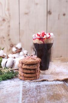 Ein glas kaffee und marshmallow wird mit sirup übergossen. kekse mit schokolade. zweig mit baumwolle auf einem hölzernen hintergrund