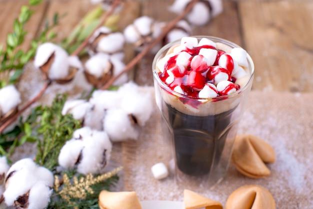 Ein glas kaffee und marshmallow wird mit sirup übergossen. kekse mit traditionellen weihnachtswünschen. zweig mit baumwolle auf einem hölzernen hintergrund
