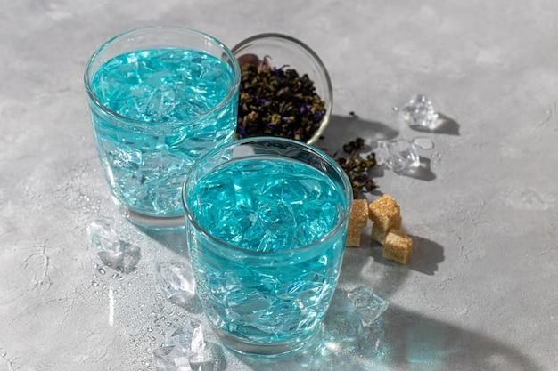 Ein glas kalter, blauer tee mit erbsenblüten und eis. blaue erbsen. für gesundes trinken, entgiftung des körpers. grauer tisch.