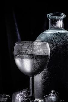 Ein glas kalter wodka oder alkohol auf dem hintergrund einer schönen flasche mit tropfen. vertikales foto.