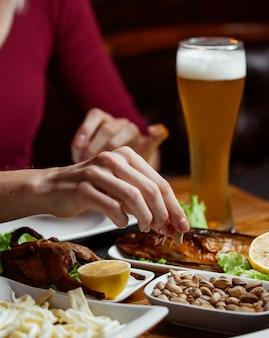 Ein glas kaltes bier mit schaum und snacks dazu