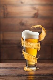 Ein glas kaltes bier mit tropfen und schaum um einen spritzer auf einem dunklen holz mit kopierraum.