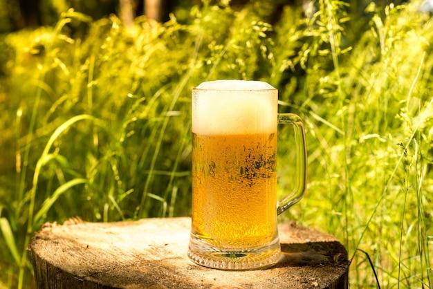 Ein glas kaltes frisches lebendes bier. bier im wald.