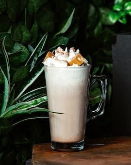 Ein glas kaltes kaffeegetränk, garniert mit schlagsahne und karamell mit nüssen