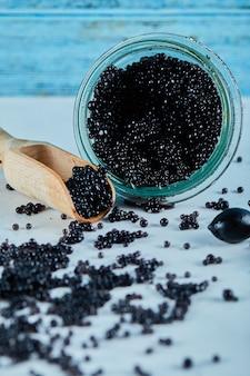 Ein glas kaviar an einer blauen wand.