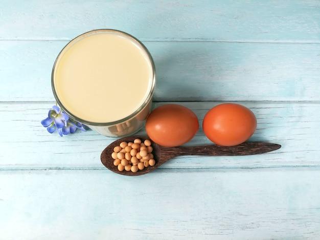 Ein glas köstliche sojamilch mit sojabohnensamen im löffel und hühnerei sind auf blau woo