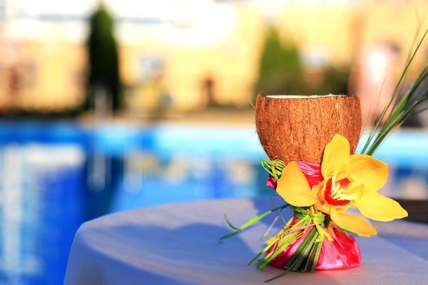 Ein glas kokosnuss verziert mit orchidee