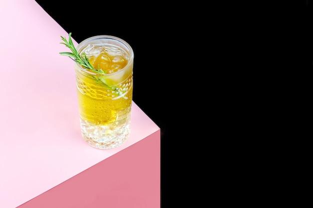 Ein glas kombucha-cocktail mit eis und einem zweig rosmarin