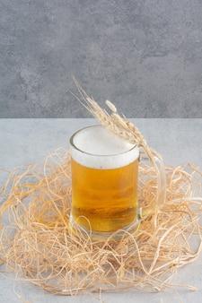 Ein glas leckeres bier mit weizen auf heu.