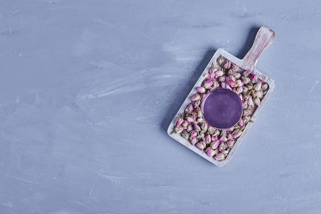 Ein glas lila getränk mit blüten in einer holzplatte, draufsicht.