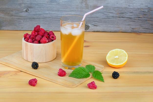 Ein glas limonade mit eis auf einem gedeckten holztisch.