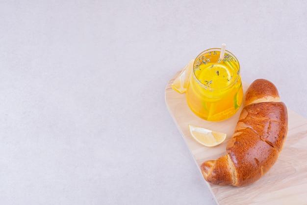 Ein glas limonade mit süßen brötchen auf weißer platte.