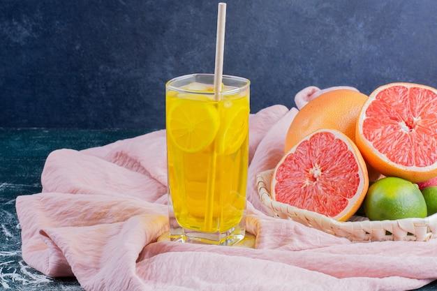 Ein glas limonade mit zitronenscheiben und grapefruits auf marmoroberfläche.