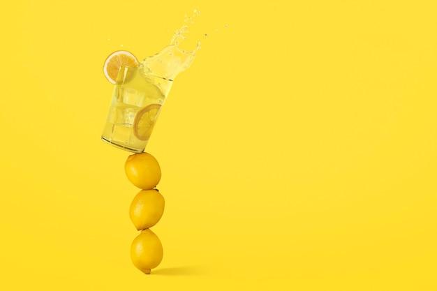 Ein glas limonade steht im gleichgewicht auf zitronen und steht kurz vor dem fall