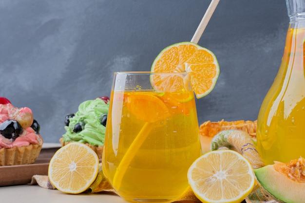 Ein glas limonade und cremige cupcakes auf dem tisch.