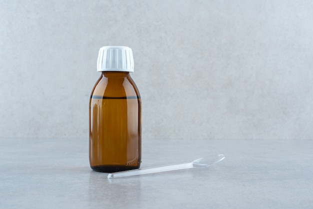 Ein glas medizingetränk mit plastiklöffel