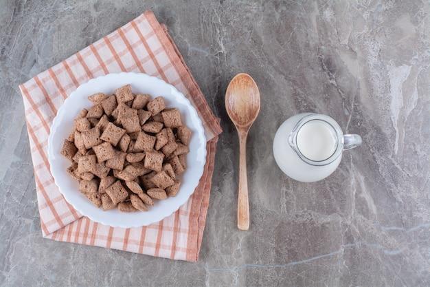 Ein glas milch mit einem weißen teller voller gesunder cerealien.