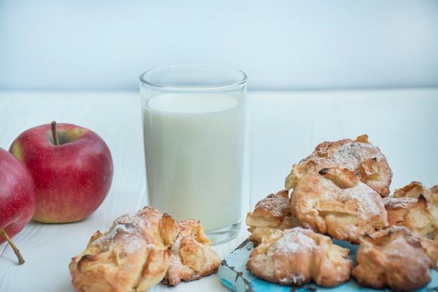 Ein glas milch mit hausgemachten apfelkeksen. kekse mit äpfeln. ein glas warme milch. gesunde lebensmittelbilanz.
