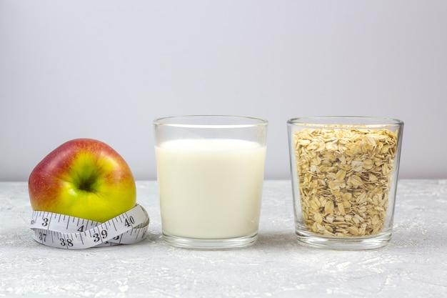 Ein glas milch und ein glas haferflocken (haferflocken). apple mit maßband.
