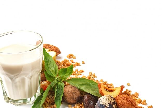 Ein glas milch und müsli mit früchten und kräutern auf einem weißen hintergrund