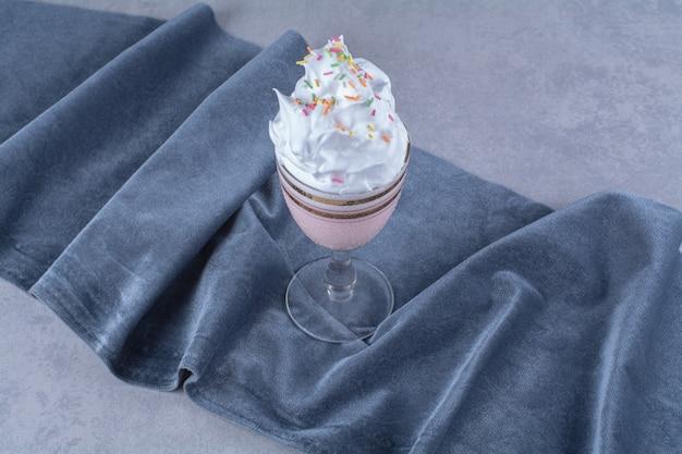 Ein glas milchshake mit zucker streuen sahne auf ein stück stoff, auf den marmor.