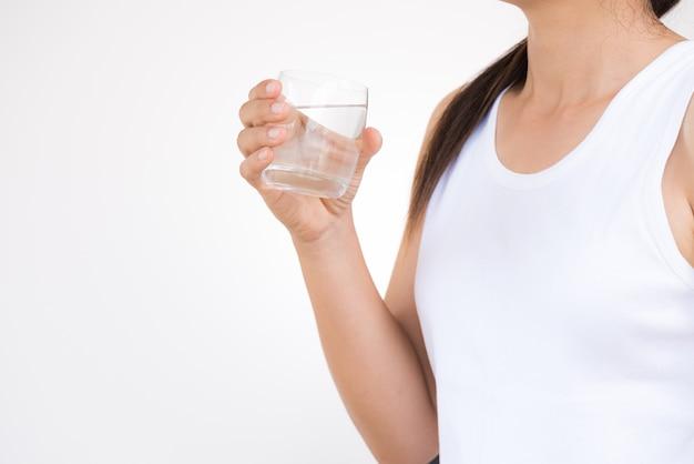Ein glas mineralwasser in den händen der frau. konzept des gesunden getränkes.