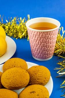 Ein glas mineralwasser, weihnachtsplätzchen, gelbes lametta auf blauem grund. weihnachts- und neujahrsdekoration.