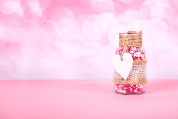 Ein glas mit bunten herzen auf einem rosa hintergrund mit bokeh