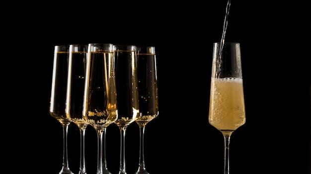 Ein glas mit champagner füllen. ein beliebtes alkoholisches getränk.