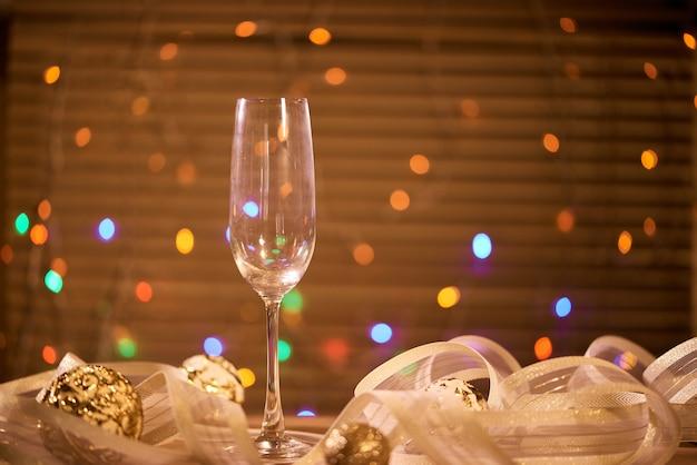 Ein glas mit champagner und goldenen weihnachtskugeln