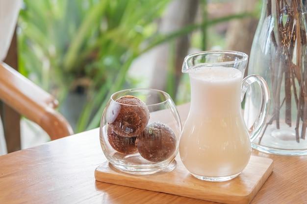 Ein glas mit drei eiskaffeebällchen auf einem holztablett, serviert mit milch, hausgemachter latte-erfrischung