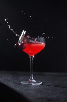 Ein glas mit einem gekühlten alkoholischen cocktail von einem barkeeper, der mit kirschen auf einer wäscheklammer und spritzern dekoriert ist. zurückhaltend