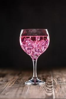 Ein glas mit einem rosa cocktail gefüllt mit eis auf dunkler oberfläche