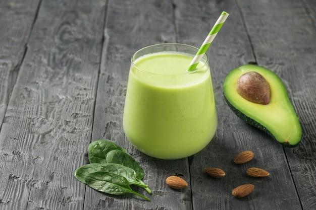 Ein glas mit einem smoothie aus mandelmilch, avocado und spinat. fitnessprodukt. diätetische sporternährung.