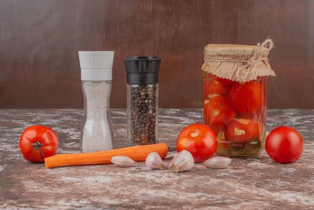 Ein glas mit eingelegten tomaten, pfefferkörnern und frischem gemüse auf einem marmortisch.