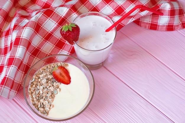 Ein glas mit erdbeerjoghurt, ein tiefer teller müsli mit erdbeeren stehen auf einem zarten rosa holzhintergrund, auf dem ein baumwolltuch in einem rot-weißen käfig liegt