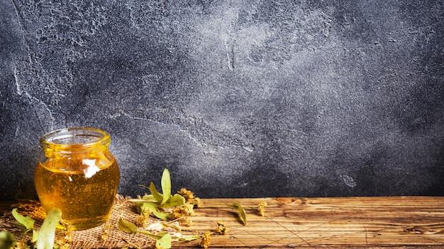 Ein glas mit flüssigem honig aus lindenblüten und ein stock mit honig auf dunklem hintergrund. speicherplatz kopieren