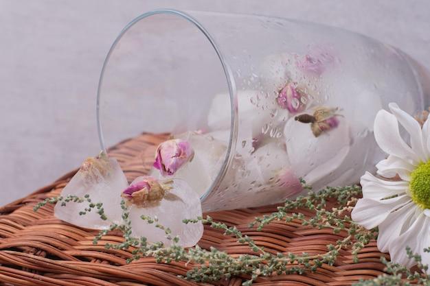 Ein glas mit kleinen rosen im eis auf weißem tisch.