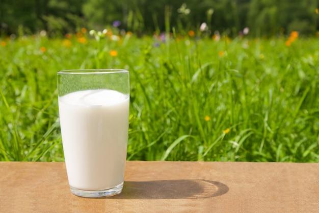 Ein glas mit milch steht an einem sonnigen tag im sommer auf dem tisch vor dem hintergrund von grünem gras und blumen.