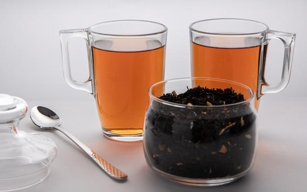 Ein glas mit schwarzen teeblättern, zwei tassen tee und löffel, teezeit für zwei