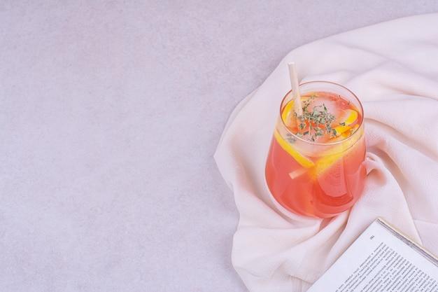 Ein glas orangensaft mit kräutern und gewürzen