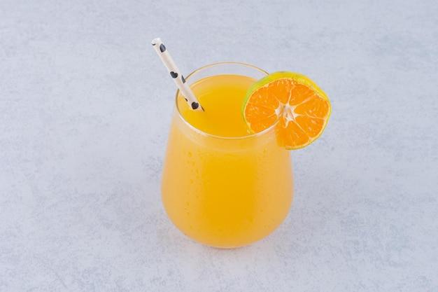 Ein glas orangensaft mit strohhalm auf steinhintergrund. foto in hoher qualität