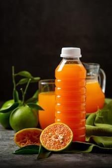 Ein glas orangensaft und frisches obst auf dem boden mit eiswürfeln.