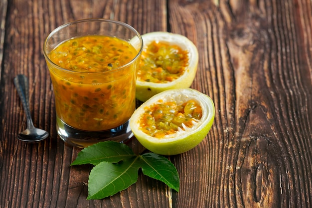 Ein glas passionsfruchtsaft und frische passionsfrucht, halbiert auf holzboden