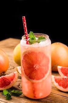 Ein glas reife grapefruit mit saft auf holztischnahaufnahme
