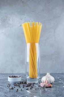 Ein glas rohe trockene spaghetti mit knoblauch- und pfefferkörnern.