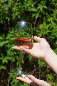 Ein glas rosa wein in den händen eines mädchens vor dem hintergrund grüner blätter
