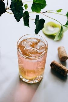 Ein glas roséwein in einem kristallglas auf marmor, grünem efeu und heller sonne
