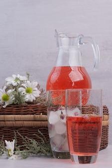 Ein glas rote limonade mit blumen auf weißem tisch.