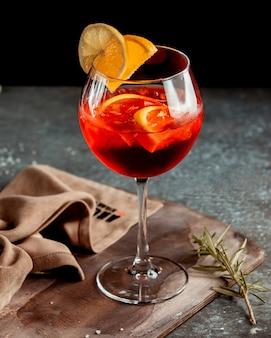 Ein glas roter cocktail, garniert mit orangenscheiben